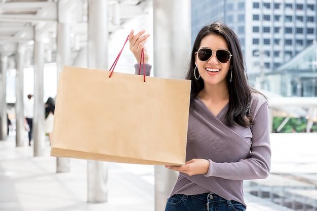 Junge asiatische frau, die ihre einkaufstasche zeigt