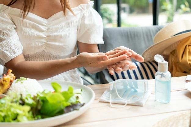 Junge asiatische frau, die ihre hände durch desinfektionsgel vor dem essen im restaurant reinigt