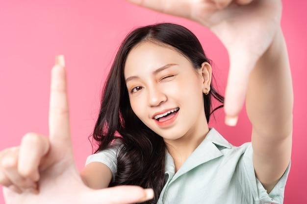 Junge asiatische frau, die ihre hände verwendet, um einen rahmen auf rosa zu bilden