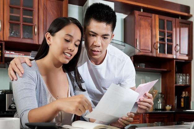 Junge asiatische frau, die ihrem ehemann rechnungen zeigt