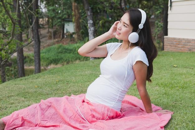 Junge asiatische frau, die im frischen frühlingsgras sitzt, musik hört und mit vergnügen lächelt.