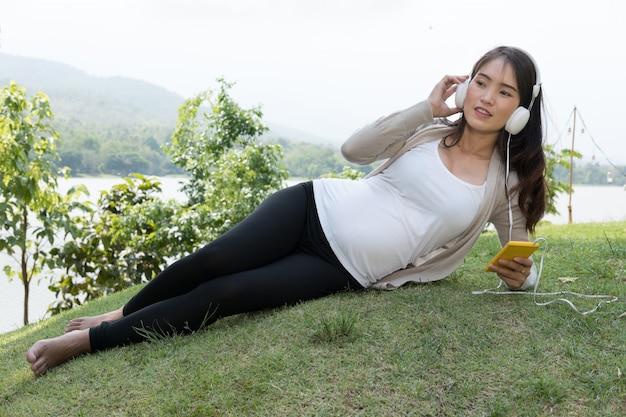 Junge asiatische frau, die im frischen frühlingsgras sitzt und musik auf ihrem handy hört, das mit vergnügen lächelt