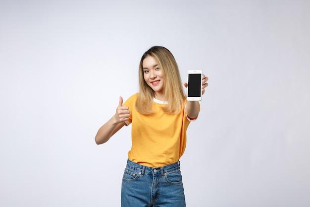 Junge asiatische frau, die im gelben hemd trägt, zeigt daumen hoch zeichen