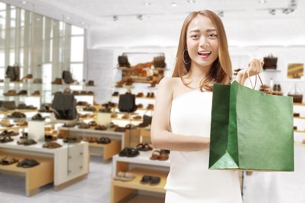 Junge asiatische frau, die im geschäft einkaufstaschen hält