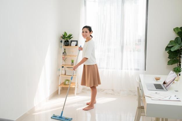 Junge asiatische frau, die im innenministerium die reinigung tut.