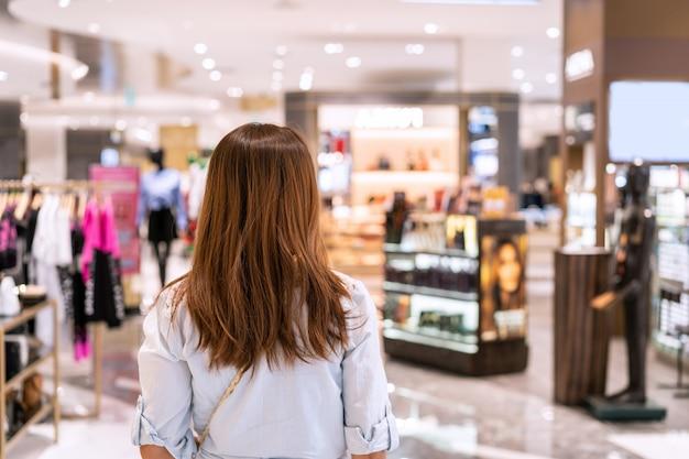 Junge asiatische frau, die im kleiderladen am einkaufszentrum, frauenlebensstilkonzept geht