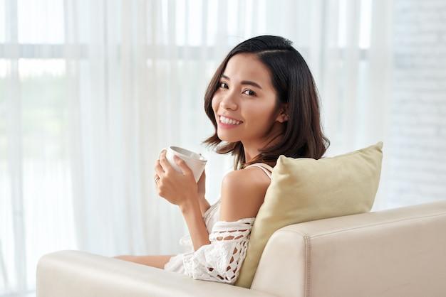 Junge asiatische frau, die im lehnsessel mit dem tasse kaffee betrachtet kamera sitzt
