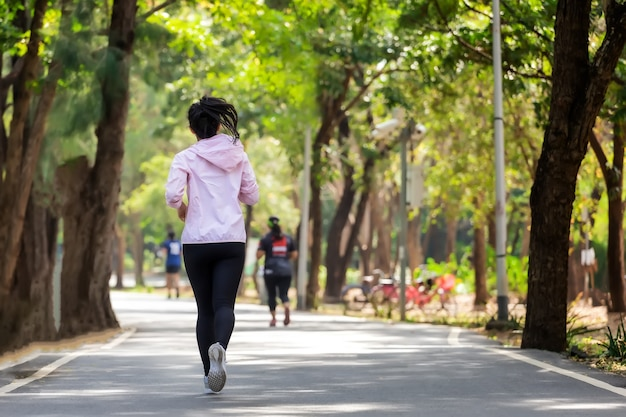 Junge asiatische frau, die im park auf straße in sportbekleidung läuft.
