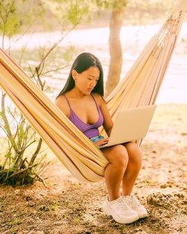 Junge asiatische frau, die in der hängematte nahe fluss sitzt und auf laptop freiberuflich arbeitet