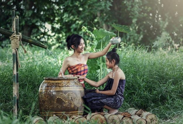 Junge asiatische frau, die in der tropischen sommerzeit badet