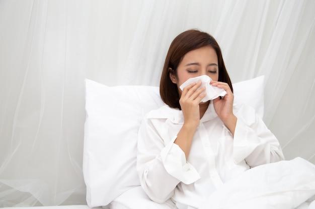Junge asiatische frau, die in einem taschentuch auf dem weißen bett im schlafzimmer niest
