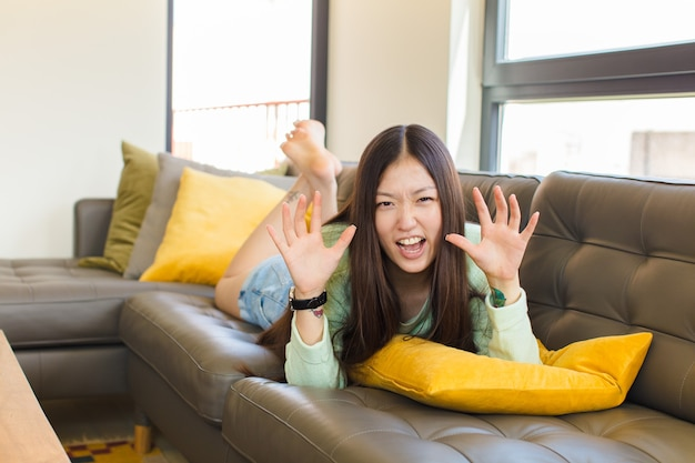 Junge asiatische frau, die in panik oder wut schreit, schockiert, verängstigt oder wütend, mit händen neben kopf