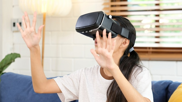 Junge asiatische frau, die in vr-kopfhörer oben schaut und versucht, gegenstände im wohnzimmer der virtuellen realität zu hause zu berühren, jugendlichmädchen, das vr-kopfhörer, leute und technologie der virtuellen realität der freizeit spielt