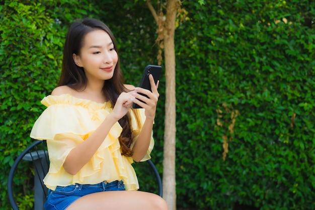 Junge asiatische frau, die intelligenten handy um natur im freien verwendet