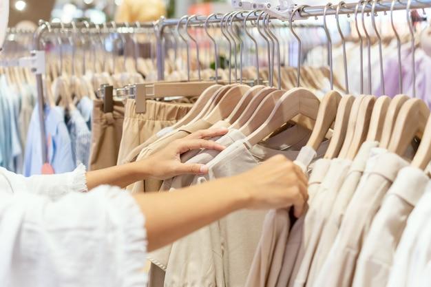 Junge asiatische frau, die kleidung im kaufhaus wählt
