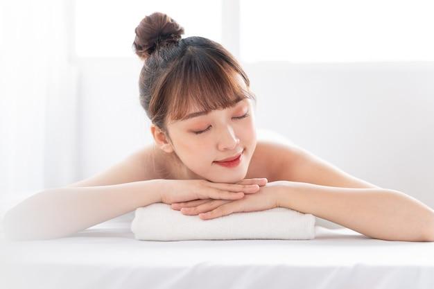 Junge asiatische frau, die körper am spa kümmert