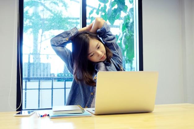 Junge asiatische frau, die körper für die entspannung beim arbeiten mit laptop-computer an ihrem schreibtisch ausdehnt