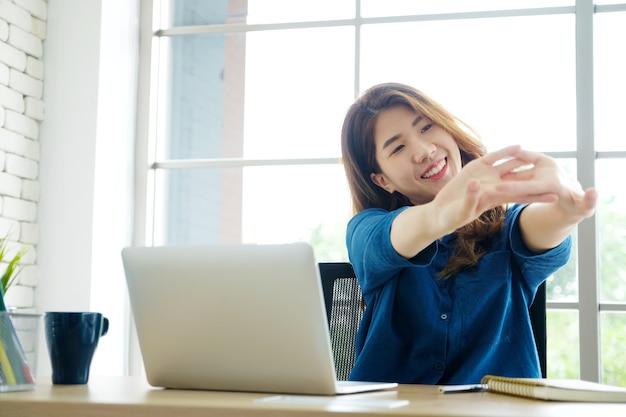 Junge asiatische frau, die körper für die entspannung beim arbeiten mit laptop-computer ausdehnt