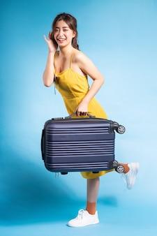 Junge asiatische frau, die koffer auf blauem sommerkonzept hält