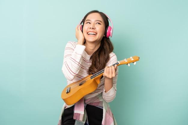 Junge asiatische frau, die kopfhörer beim spielen der ukulele verwendet