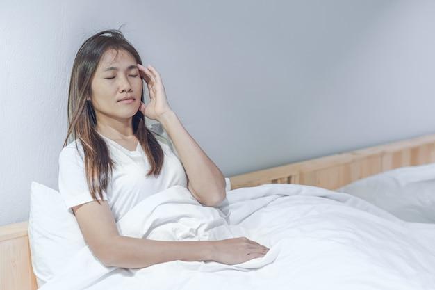 Junge asiatische frau, die kopfschmerzen und unbehagen auf weißem bett in ihrem schlafzimmer glaubt.