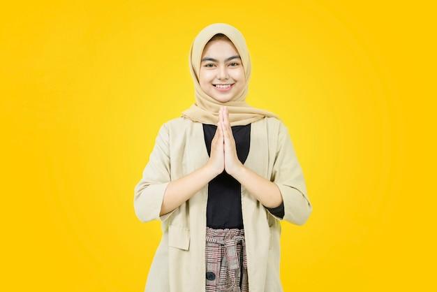 Junge asiatische frau, die kopftuch trägt, gibt grußhände mit großem lächeln auf ihrem gesicht