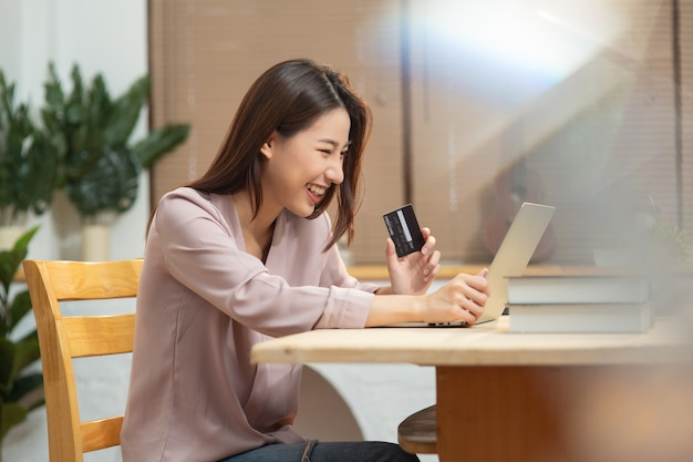 Junge asiatische frau, die kreditkarte für online-einkauf verwendet