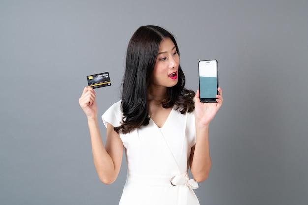 Junge asiatische frau, die kreditkarte und smartphone hält