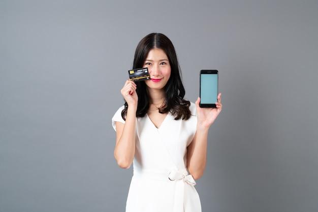 Junge asiatische frau, die kreditkarte und smartphone im weißen kleid auf grau hält