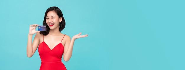 Junge asiatische frau, die kreditkarte zeigt