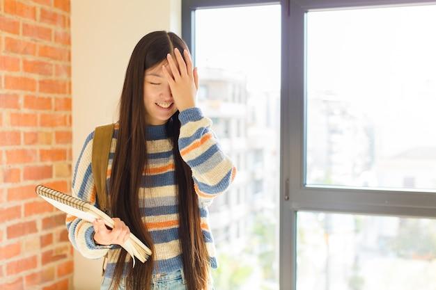 Junge asiatische frau, die lacht und auf die stirn schlägt, als würde sie sagen: oh! ich habe es vergessen oder das war ein dummer fehler
