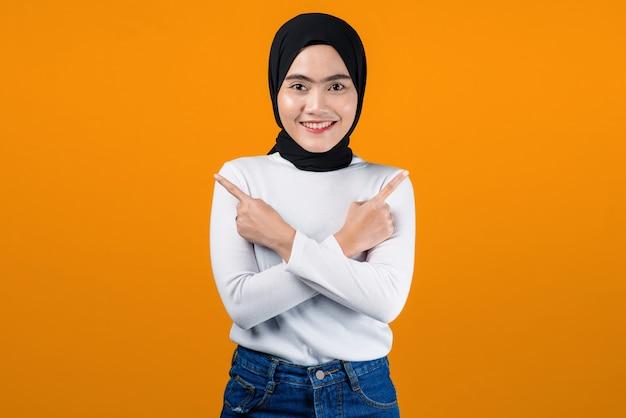 Junge asiatische frau, die lächelt und auf gelben hintergrund zeigt