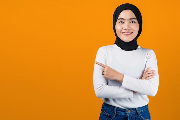 Junge asiatische frau, die lächelt und auf leeren raum zeigt