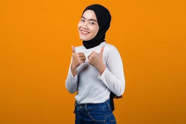 Junge asiatische frau, die lächelt und daumen gibt