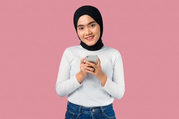 Junge asiatische frau, die lächelt und handy benutzt