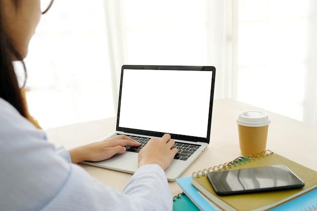 Junge asiatische frau, die laptop-computer mit leerem bildschirm für verspotten herauf schablonenhintergrund verwendet