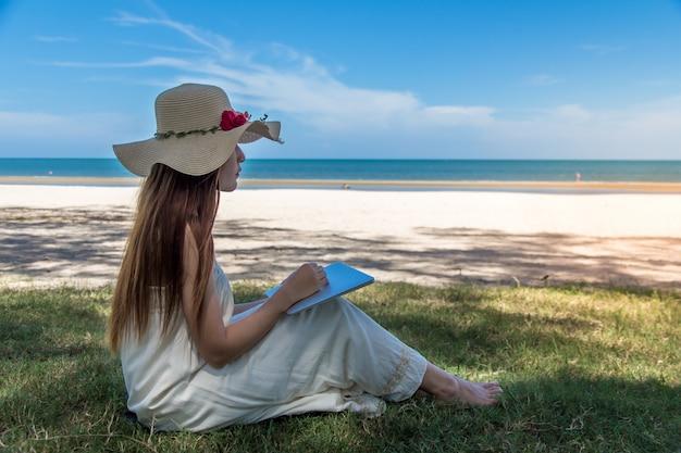 Junge asiatische frau, die laptop im kleid sitzt auf dem strand verwendet