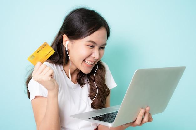 Junge asiatische frau, die laptop verwendet und kreditkarte zeigt