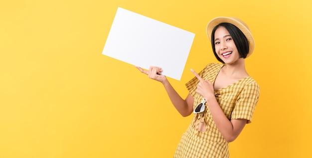 Junge asiatische frau, die leeres papier mit lächelndem gesicht hält und auf den gelben hintergrund schaut