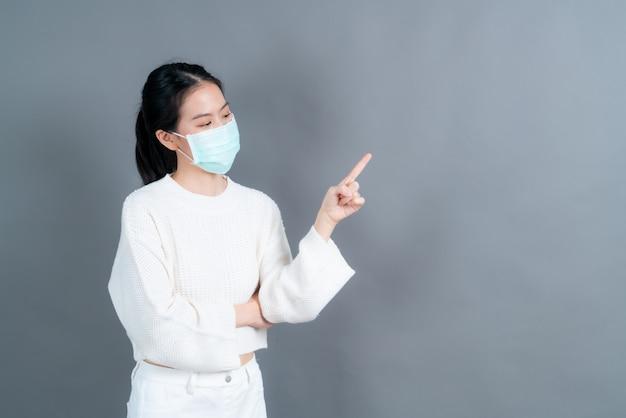 Junge asiatische frau, die medizinische gesichtsmaske und finger zeigt, die auf kopienraum zeigen