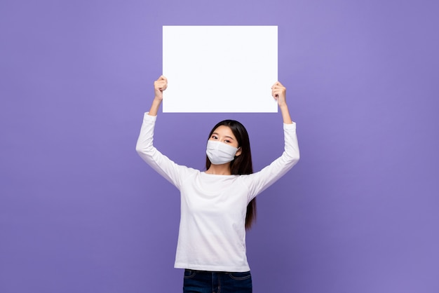 Junge asiatische frau, die medizinische maske hält, die weiße papierplatte mit leerem raum für text über kopf hält