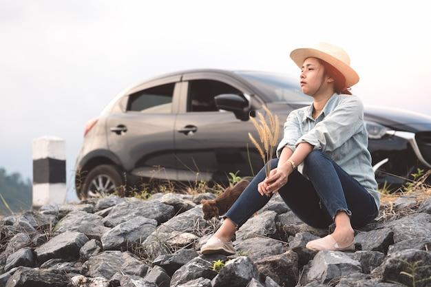 Junge asiatische frau, die mit chihuahuahunden mit schwarzem hecktürmodell eco auto sitzt.