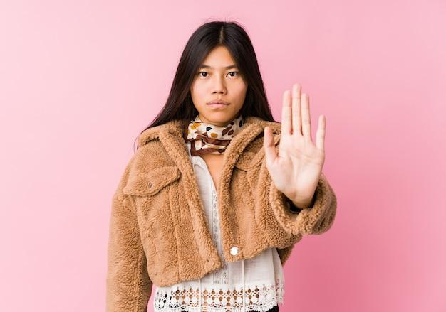 Junge asiatische frau, die mit der ausgestreckten hand zeigt das stoppschild, sie verhindernd steht.