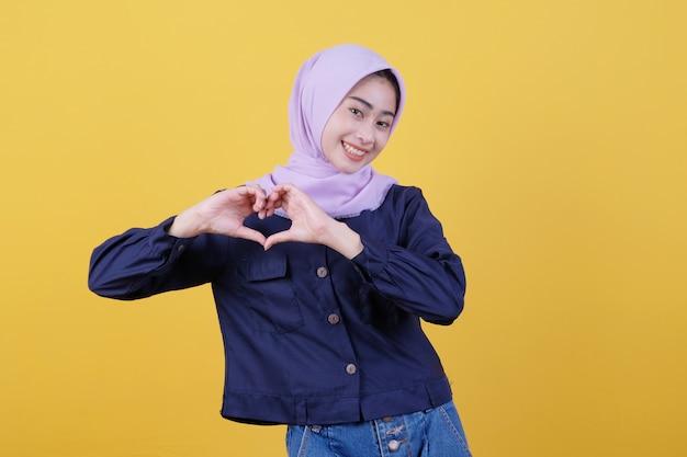 Junge asiatische frau, die mit einem fröhlichen lächeln im gesicht positiv ist und einen hijab trägt und legere kleidung im zimmer trägt, ist gelb und gibt lieben