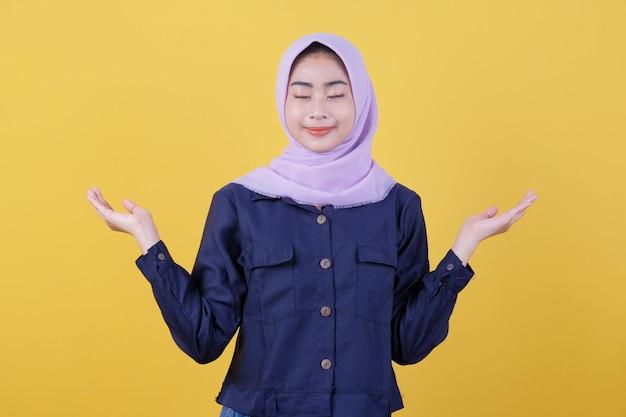 Junge asiatische frau, die mit einem fröhlichen lächeln im gesicht positiv ist und einen hijab und freizeitkleidung im zimmer trägt, ist gelb. schließe ihre augen
