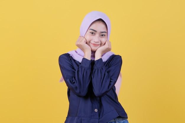 Junge asiatische frau, die mit einem fröhlichen lächeln im gesicht positiv ist und einen hijab und freizeitkleidung im zimmer trägt, ist gelb.