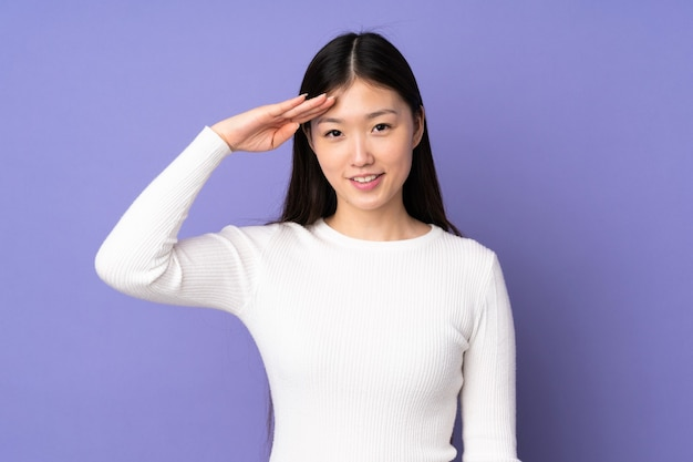 Junge asiatische frau, die mit hand salutiert