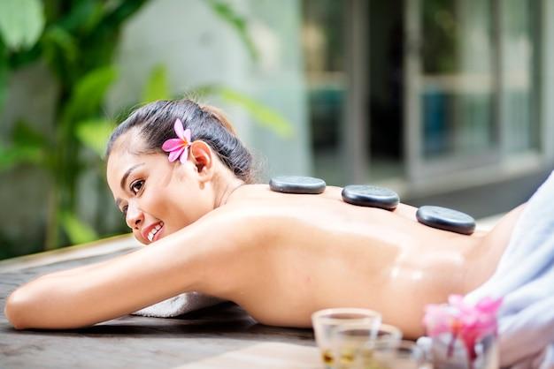 Junge asiatische frau, die mit heißer steinmassage sich entspannt