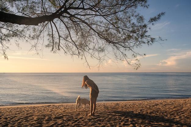 Junge asiatische frau, die mit hund unter dem baum am strand im tropischen meer im urlaub spielt