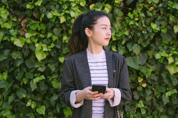 Junge asiatische frau, die mit ihrem smartphone anruft, um verbunden zu werden.